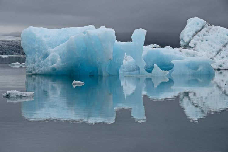 Scenic view of glaciers on lagoon against cloudy sky