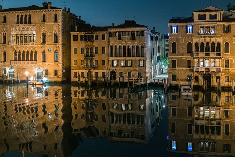 Reflection of illuminated buildings on the grand canal in venice at night.