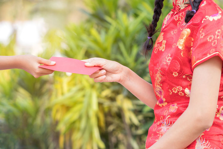 Cropped hand giving envelope to woman in park