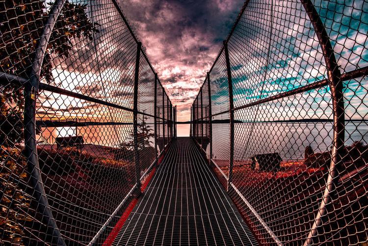 Bridge against sky seen through chainlink fence