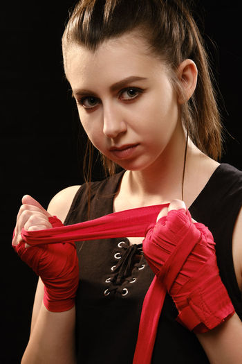 Portrait of female boxer wearing bandage against black background
