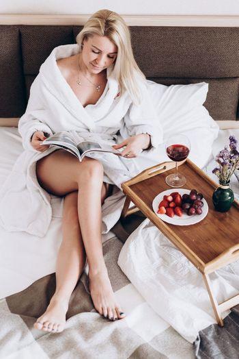 Woman In Bathrobe Reading Magazine At Home