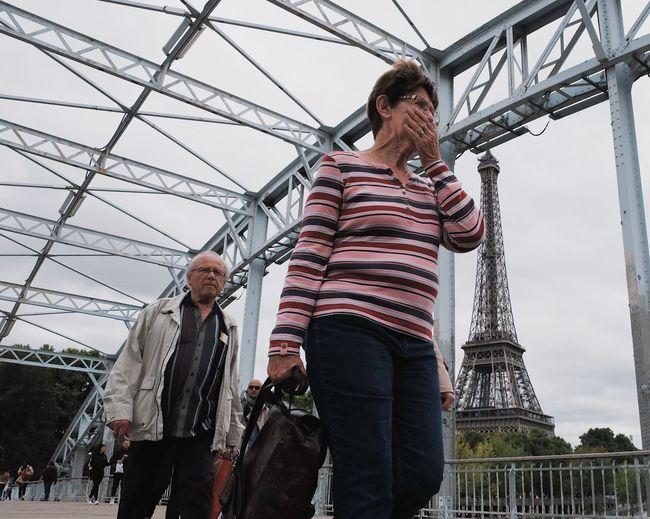 Low angle view of people walking on bridge