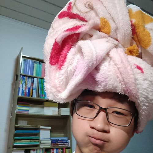 Portrait Of Smiling Boy With Wrapped Towel In Head At Home
