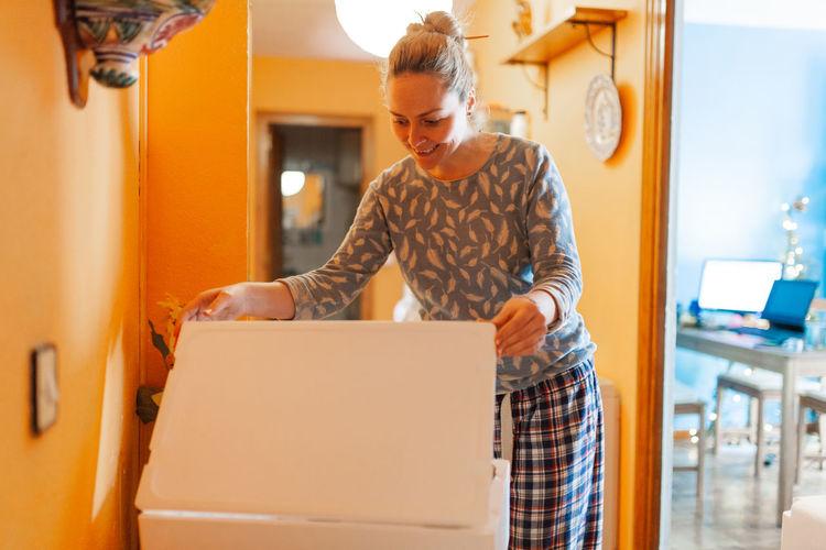 Woman opening box at home