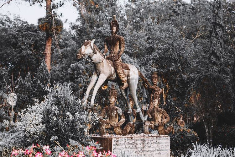 Statue amidst plants against trees