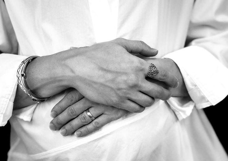 Midsection of bride showing rings with hands clasped