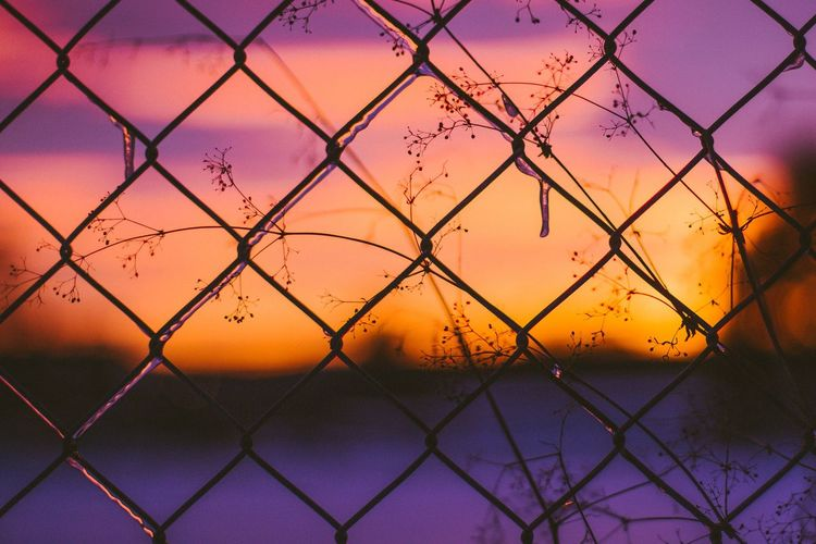 Scenic view of sea seen through chainlink fence