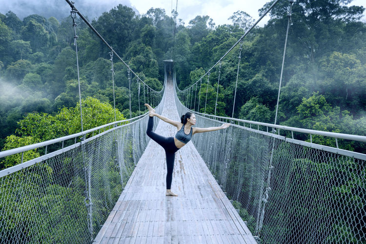 One Person Real People Tree Lifestyles Leisure Activity Plant Railing Full Length Day Balance Nature Connection Bridge Young Adult Footbridge Women Bridge - Man Made Structure Adult Casual Clothing Built Structure Outdoors