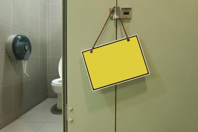 Low angle view of yellow metal hanging on wall