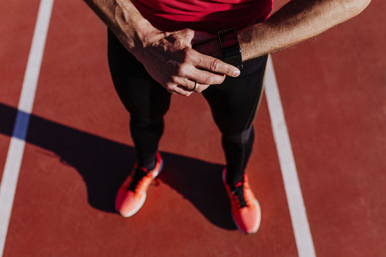 Low section of athlete wearing smart watch on sports track