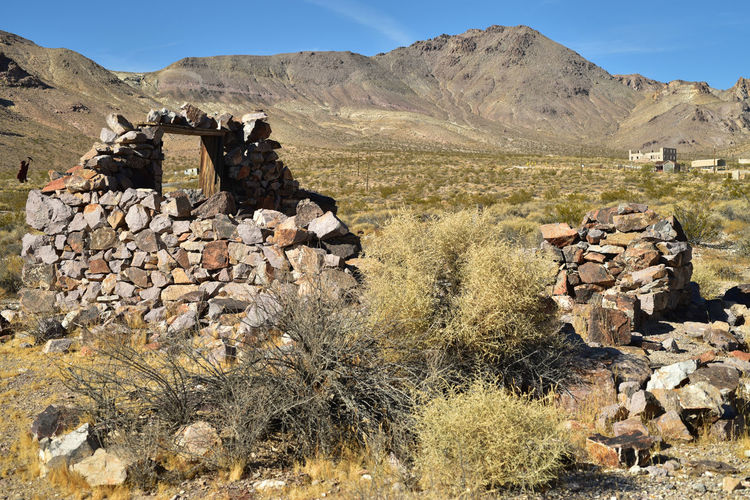 Ruins of stone house in ghost town in nevada desert landscape