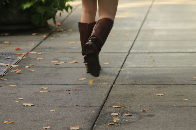 Low section of woman wearing shoes on footpath