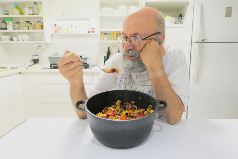 Portrait of man holding ice cream in kitchen