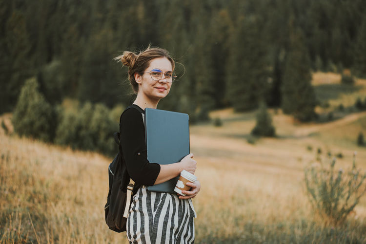 Happy woman freelancer with glasses working on laptop, remote location in nature