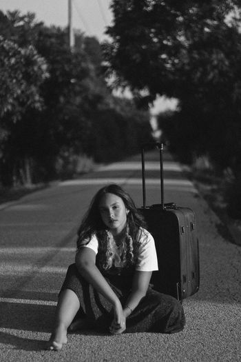 Nowhere, 2018 Beautiful Woman Black And White Contemplation Day Focus On Foreground Front View Full Length Hairstyle Leisure Activity Lifestyles Looking At Camera Nature Nowhere One Person Outdoors Plant Portrait Real People Road Sitting Teenager Transportation Tree Young Adult Young Women The Portraitist - 2018 EyeEm Awards