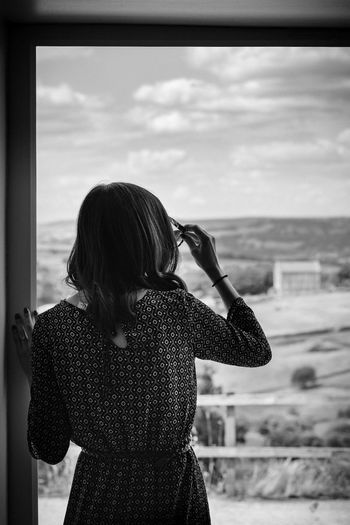 The Great Outdoors - 2018 EyeEm Awards The Portraitist - 2018 EyeEm Awards Adult Blackandwhite Cloud - Sky Contemplation Day Focus On Foreground Hairstyle Leisure Activity Lifestyles Looking Looking At View Looking Through Window Nature One Person Outdoors Real People Rear View Sky Standing Transparent Waist Up Window Women