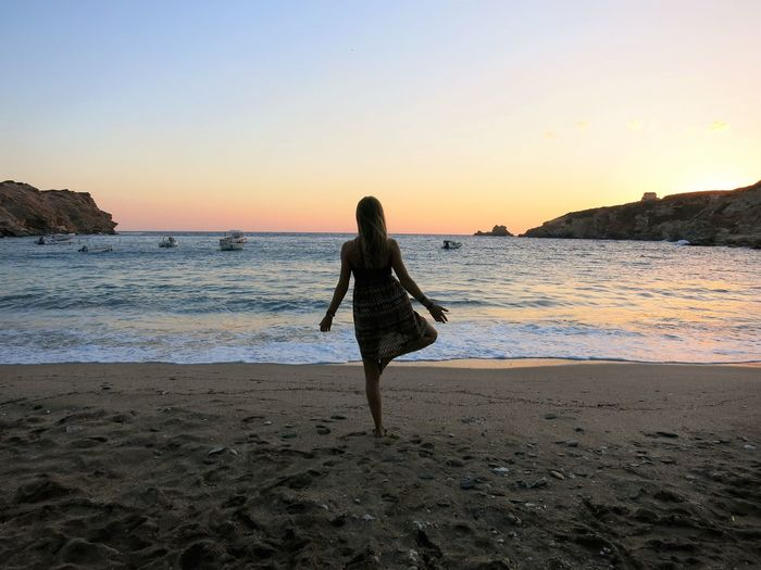 Rear view full length of woman doing yoga at beach during sunrise