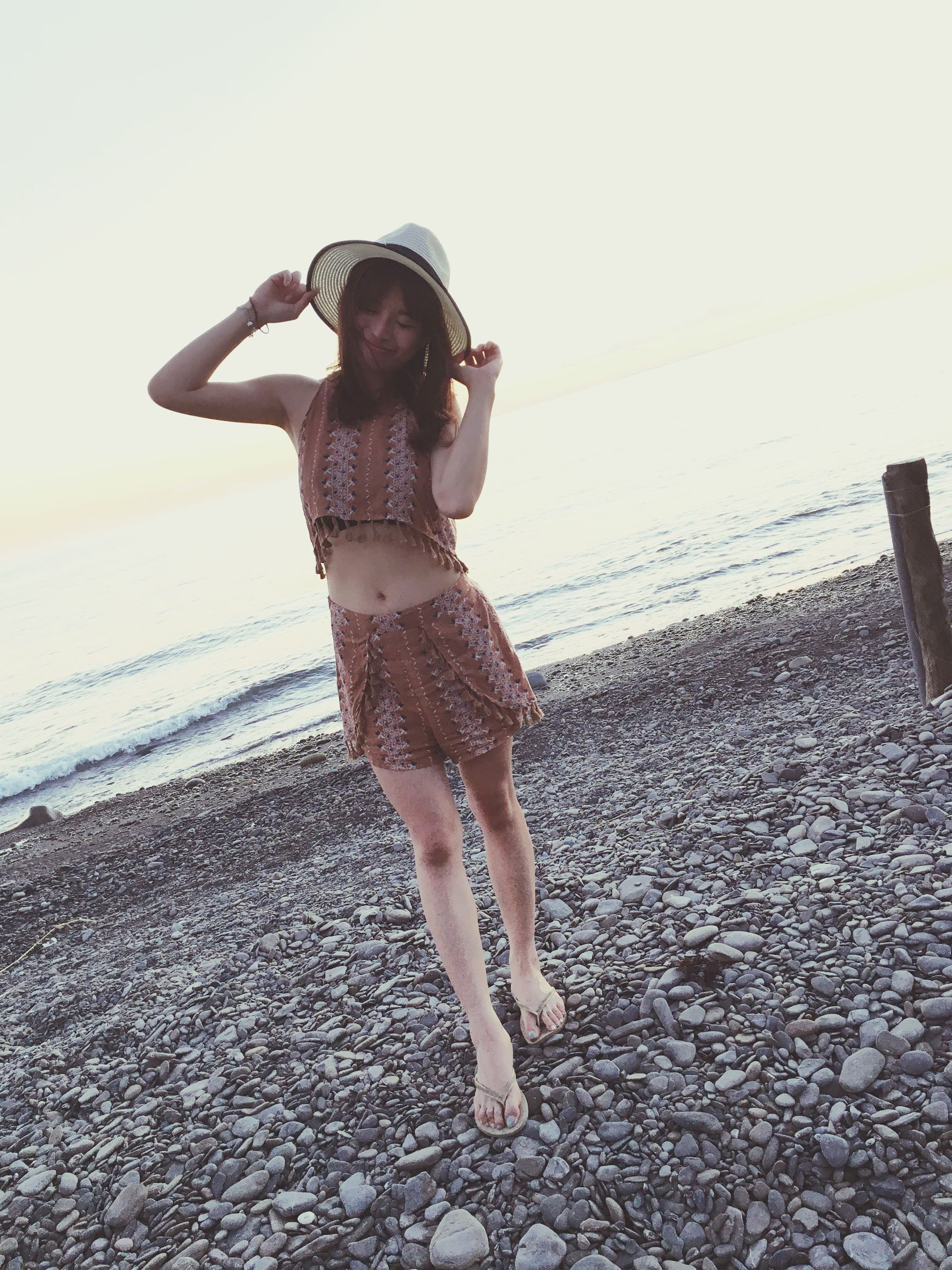 lifestyles, full length, leisure activity, beach, casual clothing, standing, young adult, person, shore, young women, front view, water, sand, sea, sunlight, looking at camera, vacations, sky