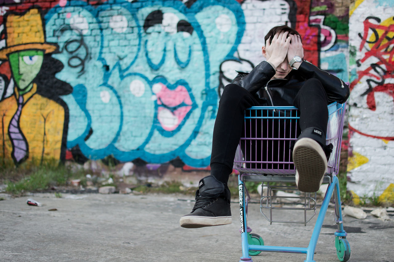 Tensed man sitting in shopping trolley
