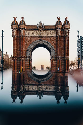 Digital composite image of arc de triomf reflecting on water