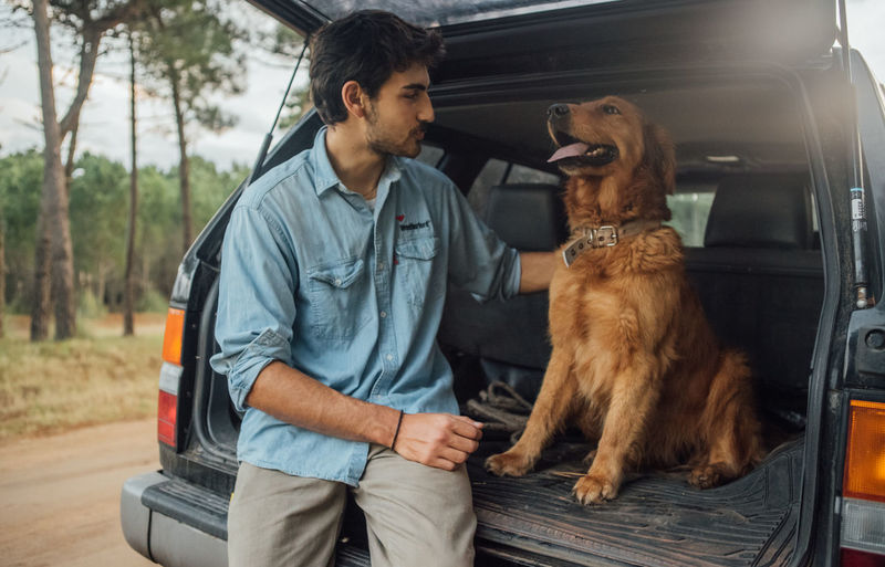 Young man with dog in car trunk