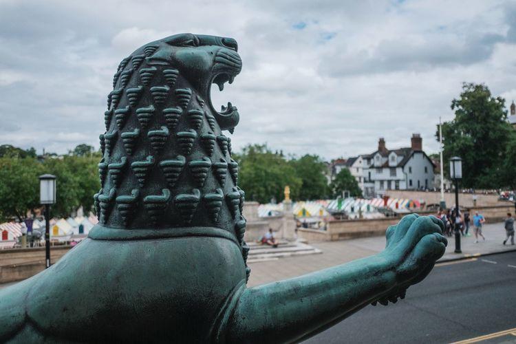 Gargoyle In City Against Cloudy Sky