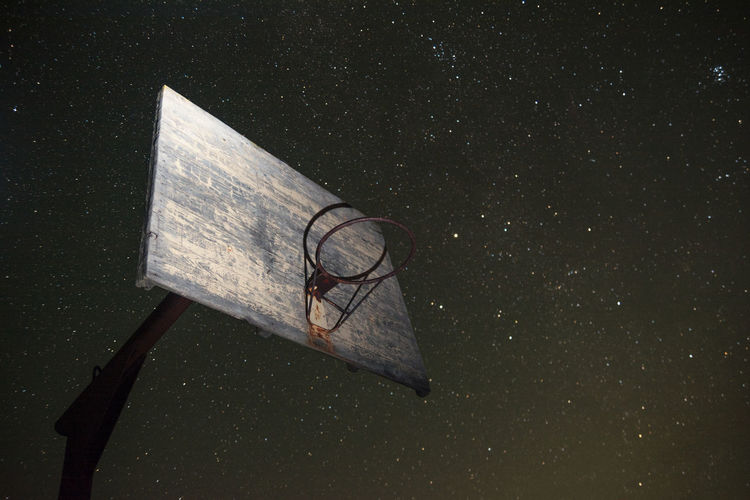 Low angle view of basketball hoop against star field in sky at night