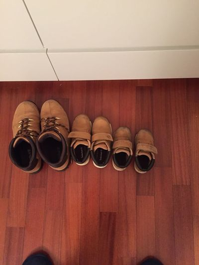 Low section of shoes on wooden floor
