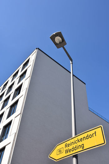 Low angle view of road sign against building