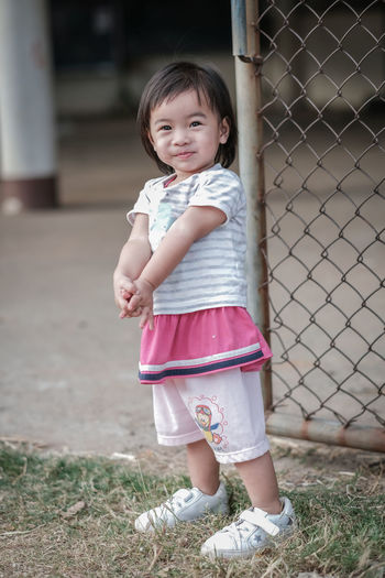 Portrait of cute girl smiling while standing on fence