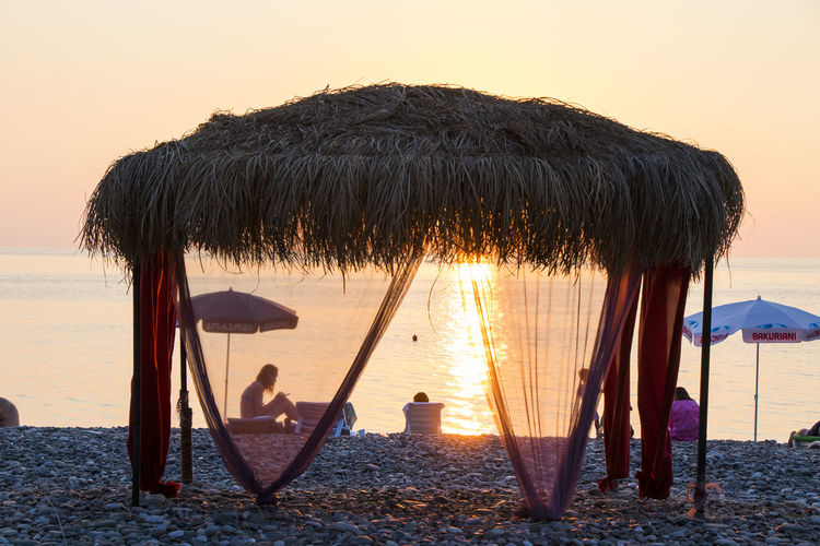 Panoramic view of beach umbrella against sky during sunset