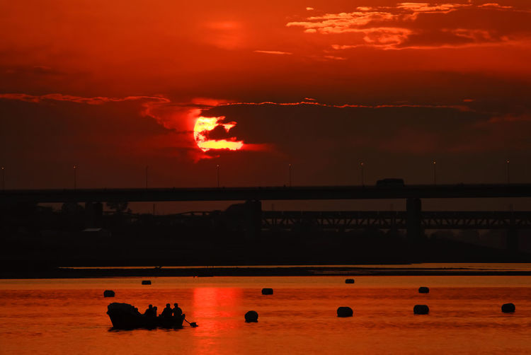Sunset and silhouette of pilgrims boat on Triveni Sangam (confluence of three rivers), Kumbh Mela festival, Allahabad known as Prayagraj, Uttar Pradesh, India. Sunset Cloud - Sky Silhouette Water Nature Beauty In Nature Scenics - Nature Outdoors Waterfront Tranquil Scene Tranquility Sunlight India Uttar Pradesh Kumbh Mela Pilgrimage Ganga Yamuna Twilight Allahabad Triveni Sangam Culture Traditional Festival Ritual