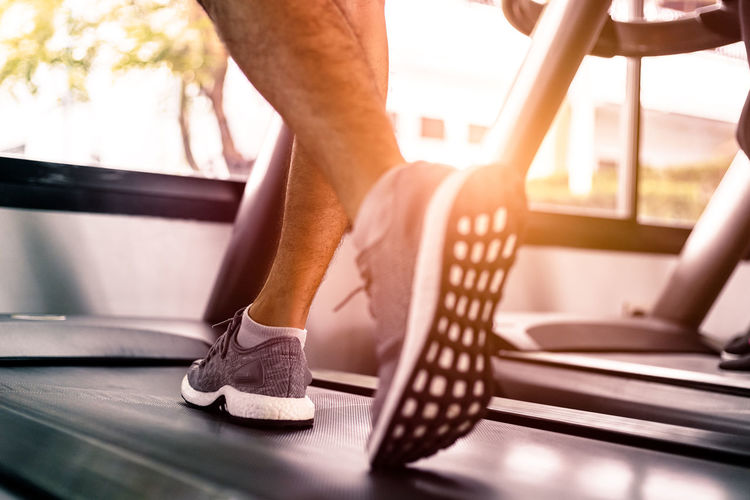 Low section of man running on treadmill