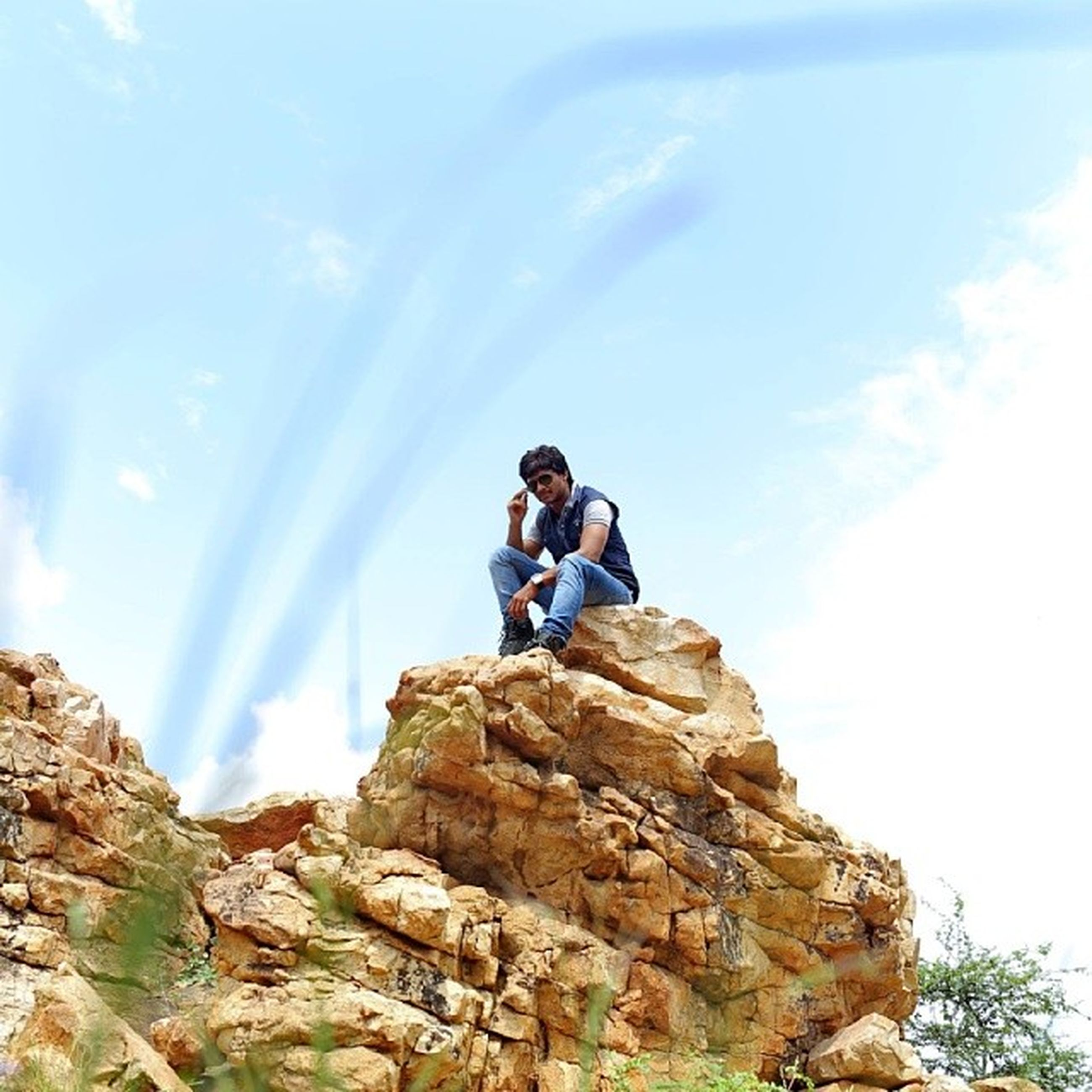 lifestyles, leisure activity, rock - object, sky, full length, young adult, casual clothing, sitting, men, young men, rock formation, low angle view, mountain, nature, standing, photography themes