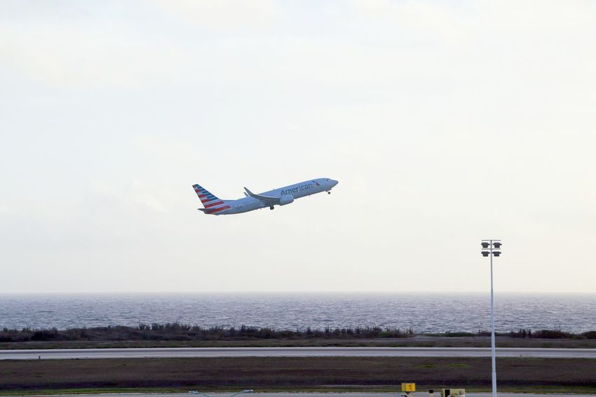American Airlines Hato Airport Take Off Air Vehicle Airplane Day Flying Horizon Mid-air Mode Of Transportation Motion No People Outdoors Plane Sky Transportation Travel Water