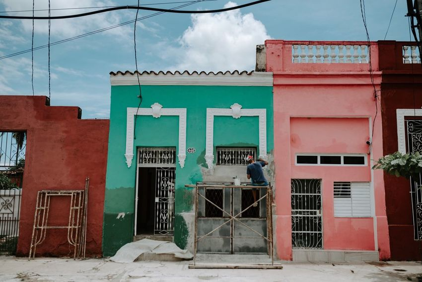 A sceen from a children's book. A man painting his house in Cuba. Painting Color Building Exterior Built Structure Architecture Text Communication Day Sky