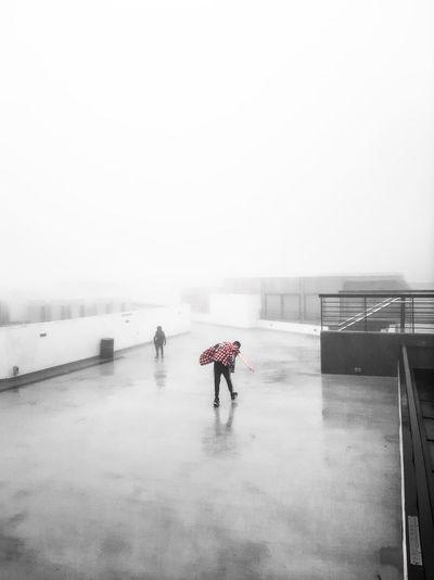 Rear view of people walking on snow against sky