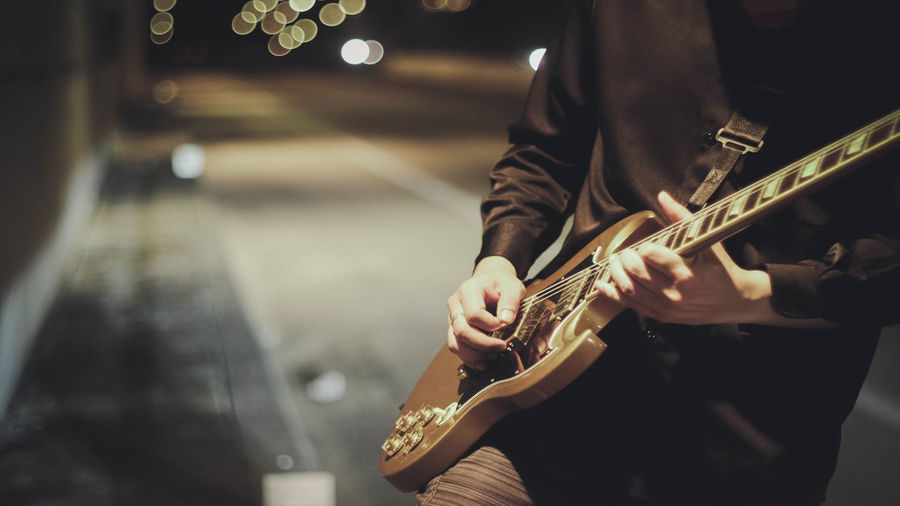 Midsection of man playing guitar on footpath at night