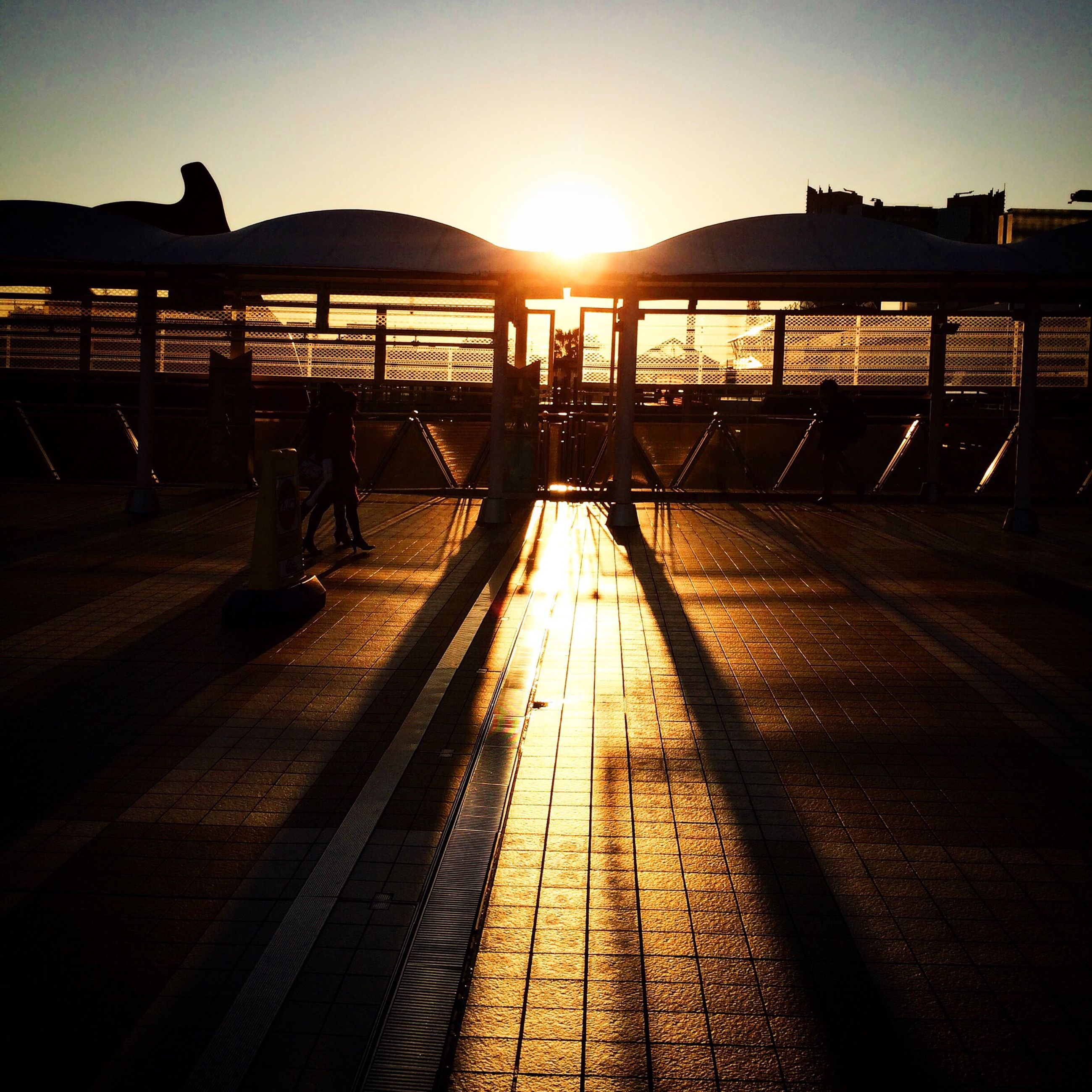 sunset, sun, sunlight, built structure, silhouette, architecture, railing, transportation, water, sky, clear sky, bridge - man made structure, connection, the way forward, incidental people, outdoors, reflection, sunbeam, shadow