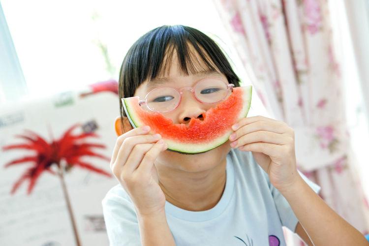 Close-up portrait of a boy eating fruit