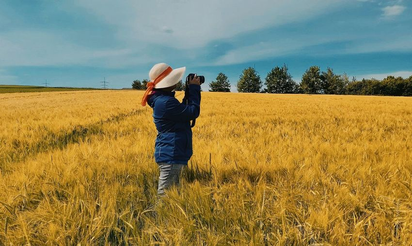 Woman photographing on field
