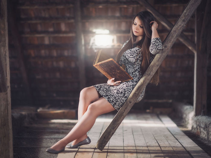 Young woman sitting reading book