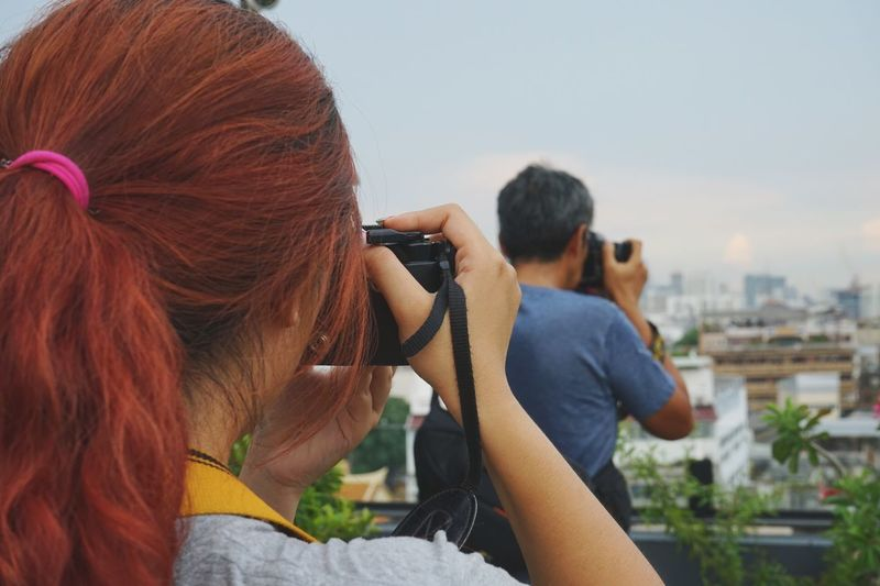 Rear view of woman photographing man against sky