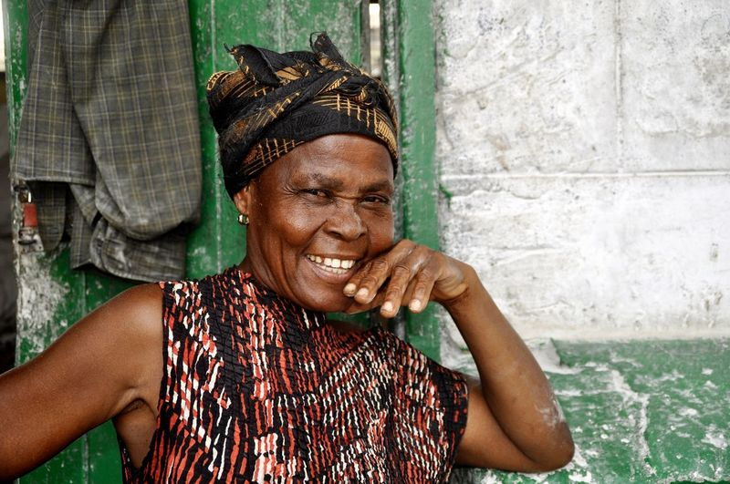 Portrait of smiling woman against wall