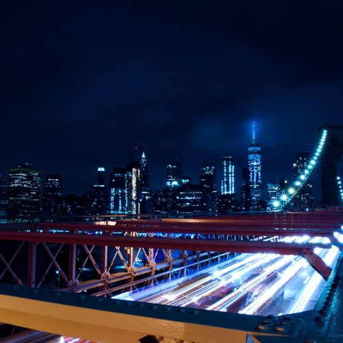 Illuminated Bridge And Buildings Against Sky At Night