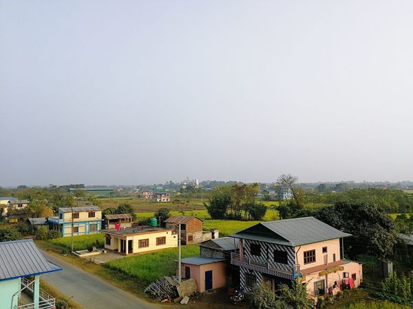 evening in town with the mustard fields in the background Mustard Fields Pollution Mustard Mustard Plant Mustard Flower Fields Of Gold EyeEm Selects House Building Exterior Architecture High Angle View Outdoors No People Residential Building Built Structure Sky Tree City Day Town Cityscape