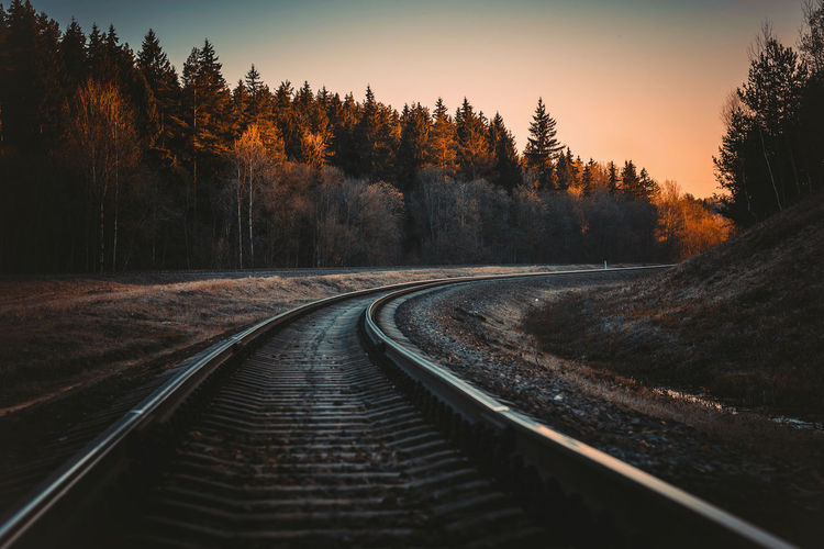 Railroad tracks by trees against sky during sunset