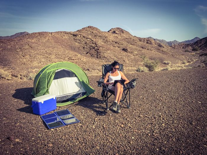Full Length Of Woman Using Laptop By Tent At Campsite Against Sky