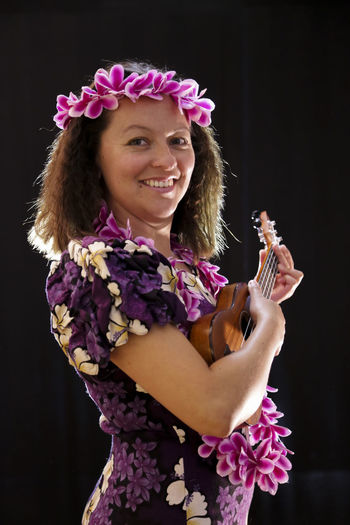 Close-up portrait of woman wearing flowers with guitar standing against wall